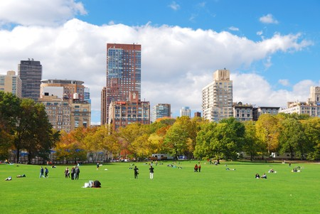 New York City Manhattan skyline panorama viewed from Central Park with cloud and blue sky and people in lawn.  photo