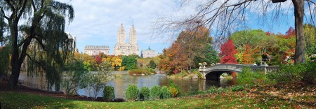 city park skyline: New York City Central Park panorama view in Autumn with Manhattan skyscrapers and colorful trees with Rainbow Bridge over lake with reflection. Stock Photo