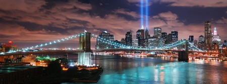 Remember September 11. New York City Manhattan panorama view with Brooklyn Bridge at night with office building skyscrapers skyline illuminated over Hudson River and two light beam in memory of September 11. Banco de Imagens