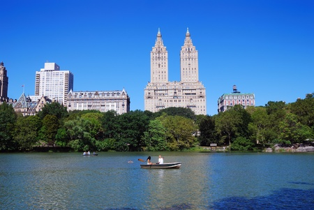 New York City Central Park with Manhattan skyline skyscrapers and blue sky with boat in lake. photo