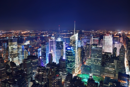 New York City Manhattan Times Square panorama aerial view at night with office building skyscrapers skyline illuminated by Hudson River. Banco de Imagens