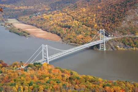 overlook: Bear Mountain bridge aerial view in Autumn with colorful trees in forest over Hudson River in New York State.