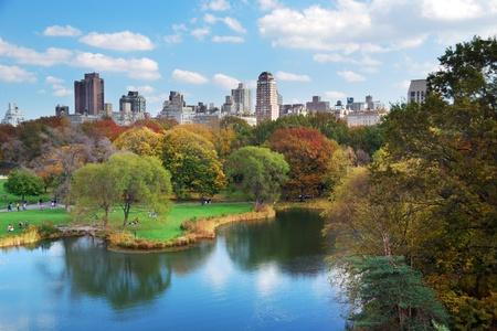 Central Park de Nueva York en otoño con los rascacielos de Manhattan y coloridos árboles sobre lago con la reflexión. Foto de archivo