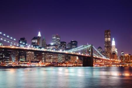 日没後の夕暮れ時のライトで照らされたハドソン川の上の高層ビルとニューヨーク市ブルックリン橋とマンハッタンのスカイライン。