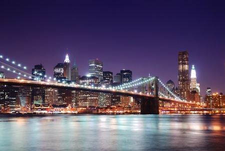 New York City Brooklyn Bridge and Manhattan skyline with skyscrapers over Hudson River illuminated with lights at dusk after sunset. Stock fotó