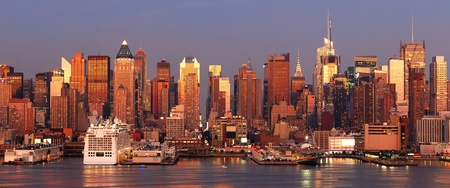 Urban city sunset. New York City Manhattan skyline panorama at sunset with Times Square and skyscrapers with reflection over Hudson river.
