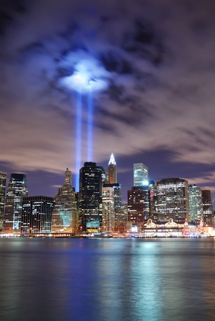 recordar: Panorama de la ciudad de Nueva York Manhattan ver por la noche con la silueta de rascacielos iluminado sobre el r�o Hudson y dos haz de luz en la memoria del 11 de septiembre de edificio de oficinas.