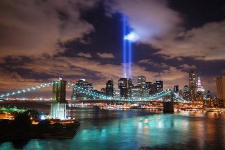 New York City Manhattan panorama view with Brooklyn Bridge at night with office building skyscrapers skyline illuminated over Hudson River and two light beam in memory of September 11. Stock Photo