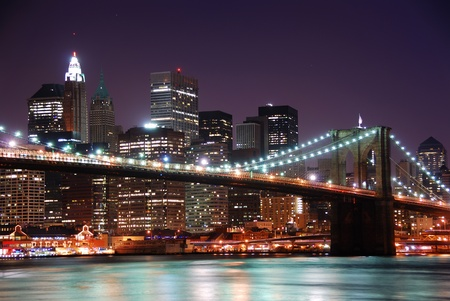 New York City Brooklyn Bridge and Manhattan skyline with skyscrapers over Hudson River illuminated with lights at dusk after sunset. Banque d'images