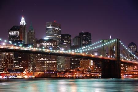 Pont de Brooklyn de New York City et Manhattan skyline avec les gratte-ciels au-dessus de la rivière Hudson, illuminé par les lumières au crépuscule après le coucher du soleil.