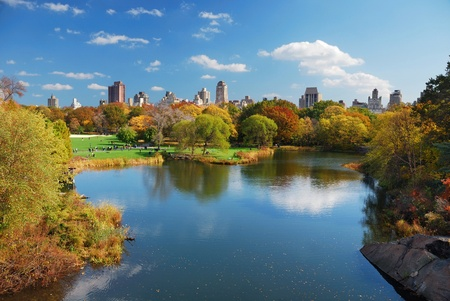 central park: New York City Central Park in Autumn with Manhattan skyscrapers and colorful trees over lake with reflection.