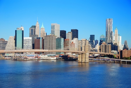 New York City Manhattan skyline with Brooklyn Bridge and skyscrapers over Hudson River in the morning after sunrise. photo