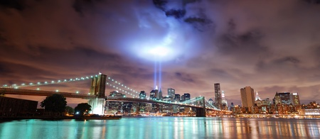 Remember September 11. New York City Manhattan panorama view with Brooklyn Bridge at night with office building skyscrapers skyline illuminated over Hudson River and two light beam in memory of September 11. 免版税图像