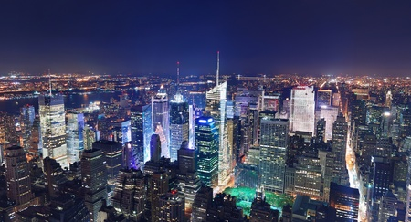 aerial view city: New York City Manhattan Times Square panorama aerial view at night with office building skyscrapers skyline illuminated by Hudson River. Stock Photo