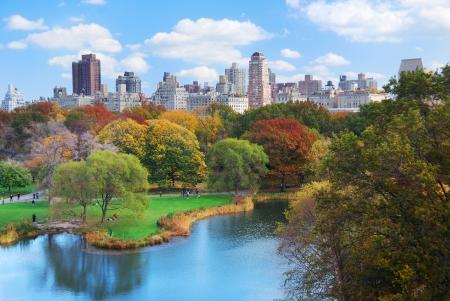 garden city: Panorama de Manhattan Central Park de Nueva York en el lago de oto�o con rascacielos y coloridos �rboles con reflexi�n.