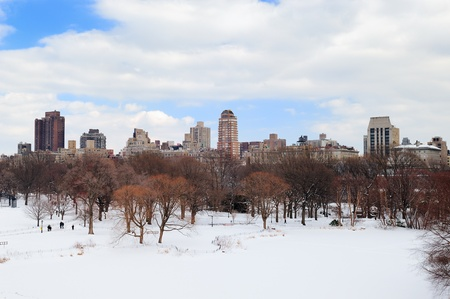 New York City Manhattan Central Park in winter with snow and city skyline with skyscrapers, blue cloudy sky. photo