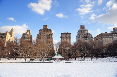 white winter: New York City Manhattan Central Park in winter with snow and city skyline with skyscrapers, blue cloudy sky.