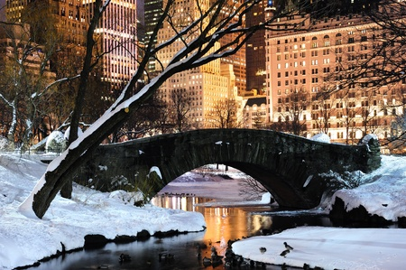 New York City Manhattan Central Park panorama in winter with snow, bridge; freezing lake and skyscrapers at dusk. Stock Photo