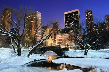 january sunrise: Panorama de Manhattan Central Park de Nueva York en invierno con la nieve, puente; Lago de congelaci�n y rascacielos al atardecer.