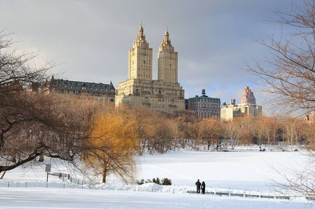 New York City Manhattan Central Park in winter with ice and snow over lake with skyscrapers and blue cloudy sky at dusk.