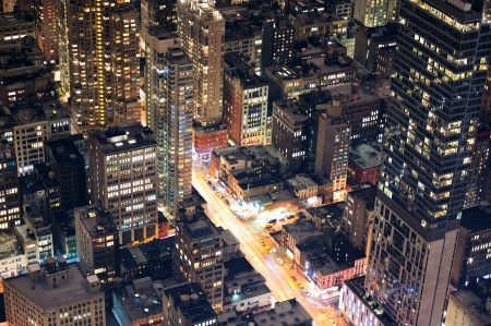 pedestrian walkway: New York City Manhattan street aerial view at night with skyscrapers, pedestrian and busy traffic.