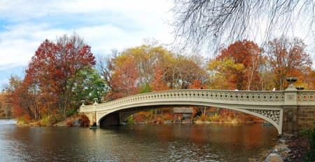 central park: New York City Manhattan Central Park panorama at Autumn with skyscrapers, foliage, lake and Bow Bridge. Stock Photo