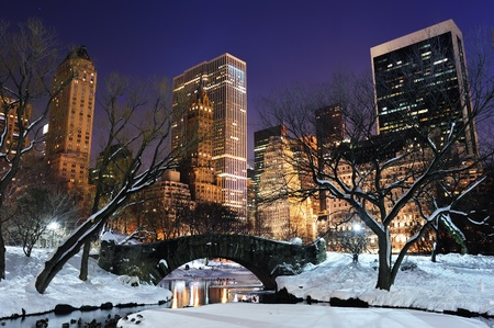 december sunrise: New York City Manhattan Central Park panorama in winter with snow, bridge; freezing lake and skyscrapers at dusk. Stock Photo