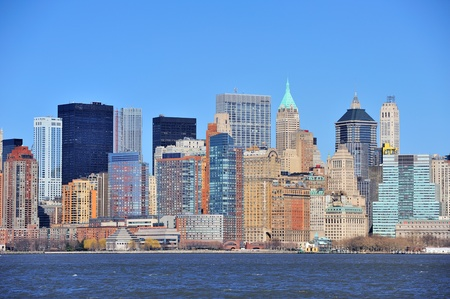 Skyscrapers of New York City Manhattan downtown with urban city skyline over Hudson River with blue clear sky photo
