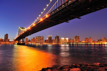 New York City Manhattan Bridge over East River at dusk illuminated with light with reflections and downtown skyline viewed from Brooklyn. photo