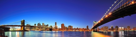 skyline city: New York City Manhattan skyline panorama with Brooklyn Bridge and Manhattan Bridge over East River at dusk illuminated with reflections and downtown skyscrapers viewed from Brooklyn.