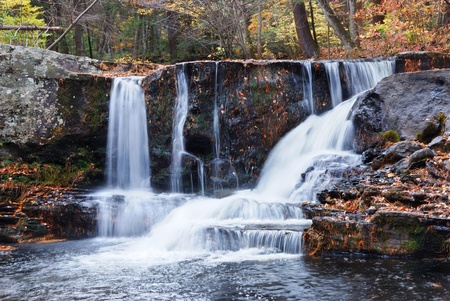 autumn colour: Waterfall with trees and rocks in mountain in Autumn. From Pennsylvania Dingmans Falls.