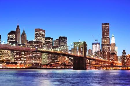 Brooklyn bridge with New York City Manhattan downtown skyline at dusk illuminated over East River with blue clear sky.