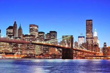 Brooklyn bridge with New York City Manhattan downtown skyline at dusk illuminated over East River with blue clear sky.