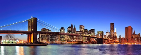 Brooklyn bridge with New York City Manhattan downtown skyline panorama at dusk illuminated over East River with blue clear sky. photo
