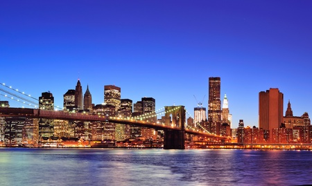 lower manhattan: Brooklyn bridge with New York City Manhattan downtown skyline at dusk illuminated over East River with blue clear sky.