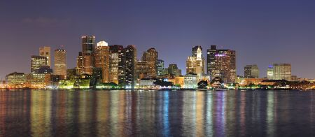 Boston downtown skyline panorama with skyscrapers over water with reflections at dusk illuminated with lights.  photo