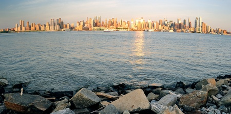 New York City Manhattan midtown skyline panorama at sunset with reflection over skyscraper and river at Shore with rocks. photo