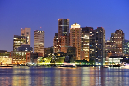 boston: Boston downtown at dusk with urban buildings illuminated at dusk after sunset.