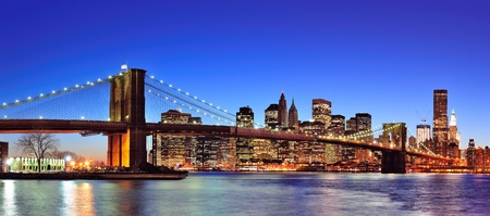 manhattan: Brooklyn bridge with New York City Manhattan downtown skyline panorama at dusk illuminated over East River with blue clear sky.