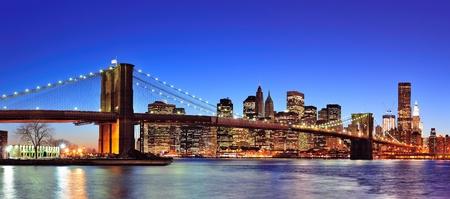 Puente de Brooklyn con panorama de horizonte el centro de Manhattan de Nueva York al anochecer iluminado sobre este río con cielo azul claro.