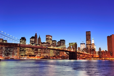 Brooklyn bridge with New York City Manhattan downtown skyline at dusk illuminated over East River with blue clear sky. photo