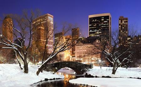 january sunrise: Panorama de Manhattan Nueva York Central Park en invierno con nieve, puente; congelaci�n de lago y rascacielos al atardecer.