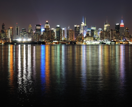 new york city times square: New York City Manhattan midtown skyline panorama at night with lights reflection over Hudson River.
