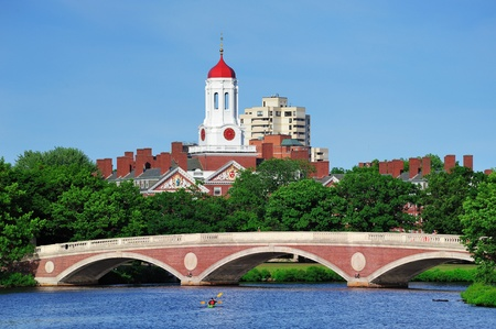 harvard: John W. Weeks Bridge and clock tower over Charles River in Harvard University campus in Boston with trees, boat and blue sky. Stock Photo