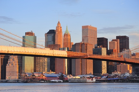 Brooklyn Bridge with lower Manhattan skyline in the morning with colorful cloud over East River in New York City photo