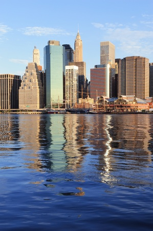 east coast: Lower Manhattan skyline panorama over East River with reflection and blue sky in New York City
