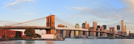 east river: Brooklyn Bridge with lower Manhattan skyline panorama in the morning with colorful cloud over East River in New York City