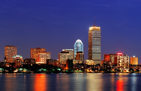 Boston city skyline at dusk with Prudential Tower and urban skyscrapers over Charles River with lights and reflections. photo