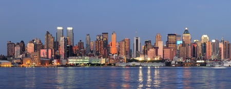 weehawken: Hudson River waterfront view of New York City Manhattan after sunset with cityscape panorama and light reflection in tranquil blue tone. Stock Photo