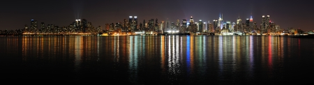 New York City Manhattan midtown skyline panorama at night with lights reflection over Hudson River.